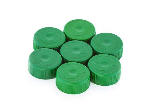 Seven green plastic bottle caps