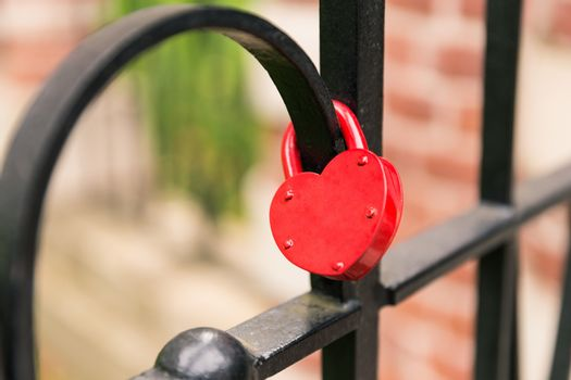 Close focus on empty red heart lock hanging on black cage meaning of forever love from lover.