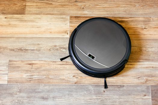 robot vacuum cleaner on the parquet floor in the apartment