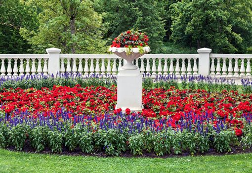 Landscaped flowerbed with blooming flowers at summer and classic style architecture details