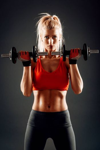 Attractive muscular girl doing exercise for biceps with dumbbells. Looking at camera.