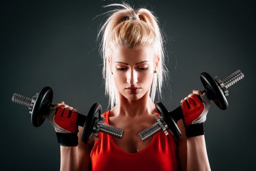Attractive muscular girl doing exercise for biceps with dumbbells. Looking down.