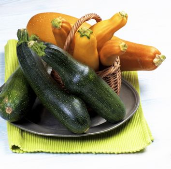 Arrangement of Green and Yellow Fresh Ripe Zucchini in Wicker Basket on Tin Plate and Napkin closeup on Wooden background