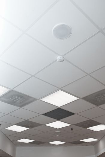 Office room ceiling with smoke detector and alarm