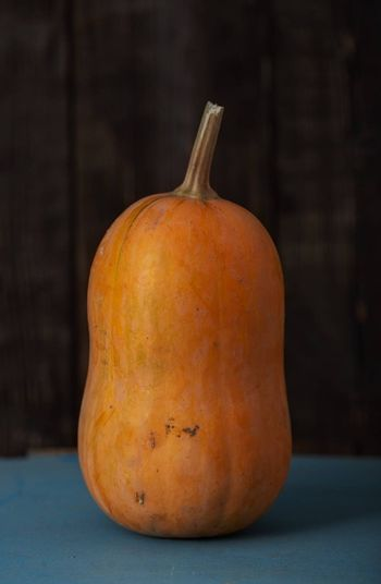 Orange pumpkin on a table. Vertical photo