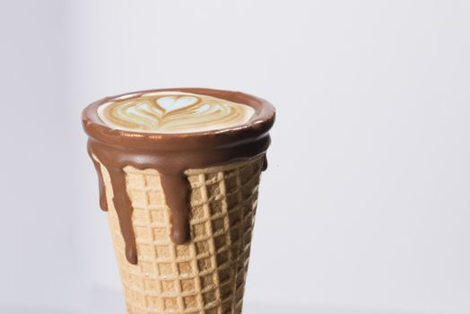 Coffee in waffle cone with drawings in capuccino / latte milk fo