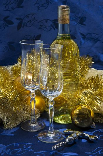 Bottle of white wine, glasses and Christmas decorations on a blue background