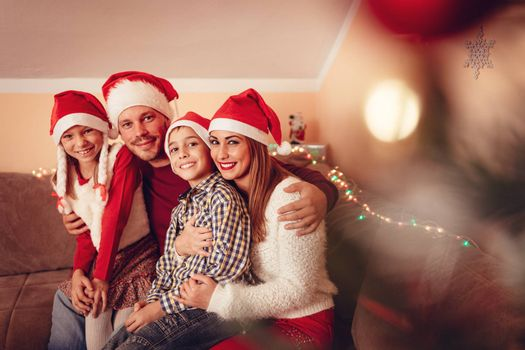Beautiful smiling family are gathered together in a Christmas eve at the home. Looking at camera and wearing santa hats.