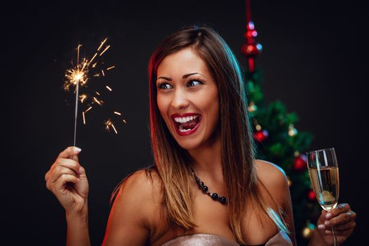 Portrait of a cheerful beautiful woman celebrating Christmas. She is having fun with sparklers and champagne.