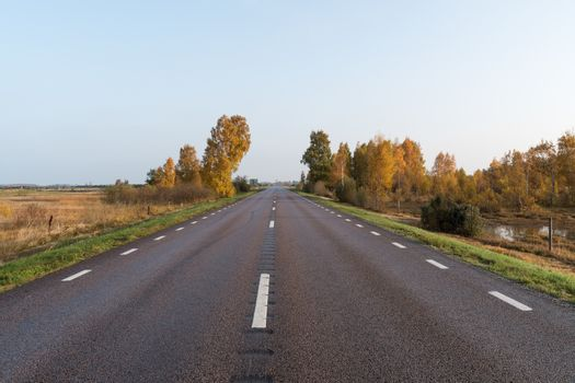 Straight road into a colorful landscape