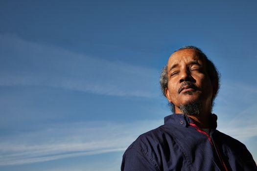 A portrait of a black rastafarian man over a blue sky gathering sun, eyes closed.
