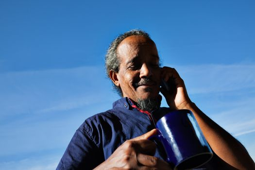 A portrait of a black rastafarian man over a blue sky with some clouds, holding a mug of tea or cofee, on the phone