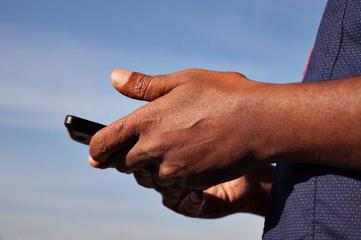 black men's hands holding phone blue sky behind