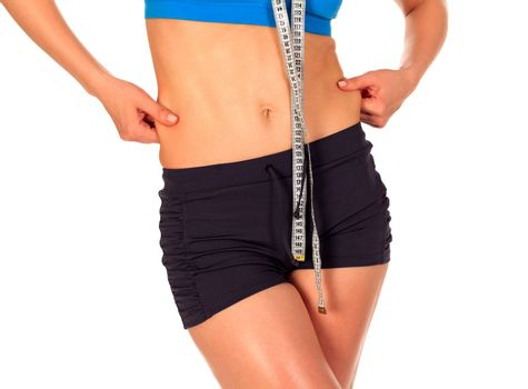 Fit woman pinches fat on her sides, isolated on white background