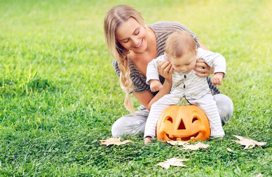 Happy young mother with her precious little son playing outdoors, cheerful baby sitting on the pumpkin with carved smiling face, Halloween holiday celebration