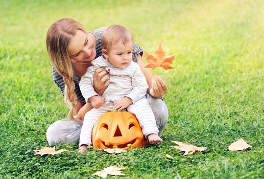 Happy young mother teaching her precious little son about autumnal leaves, cheerful baby sitting on the pumpkin decorative toy, Halloween holiday celebration