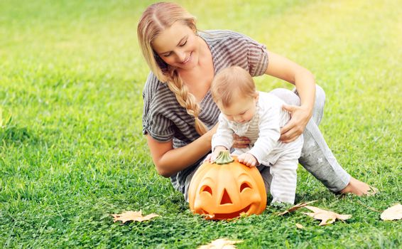 Beautiful young mother with adorable little child, playing with carved pumpkin, enjoying traditional autumn holiday, happy Halloween celebration