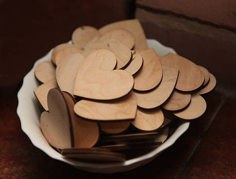 Carved wooden hearts on a white plate. Gift for Valentine's Day