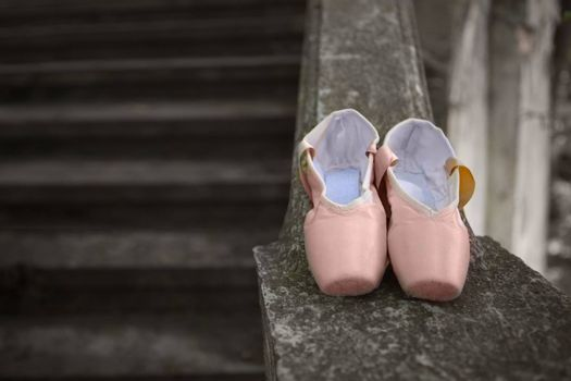 Pink pointe shoes for a classical ballerina, close-up on concrete