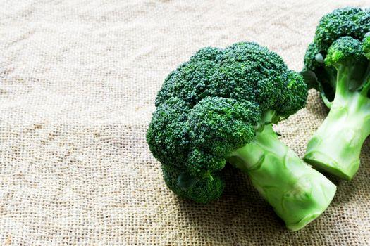 Closeup fresh broccoli on sackcloth background, raw food for coo