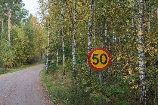 Speed limit traffic sign by a gravel road