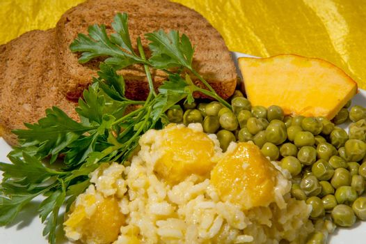 rice with cream of pumpkin with nutmeg and parsley on a colored background