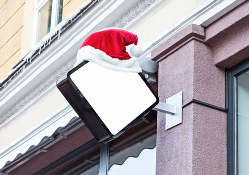 White blank outdoor company signage mockup decorated with red Santa Claus hat during Christmas holidays