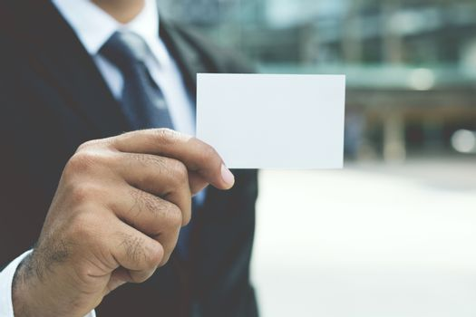 Young businessman who takes out blank business card from the pocket of his shirt business suit, copy space