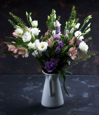 Elegant Flowers Bouquet with White and Purple Lisianthus, Alstroemeria and Decorative Green Stems in White Tin Jug closeup on Dark Grunge background