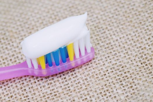 Toothbrush with toothpaste on a sackcloth background