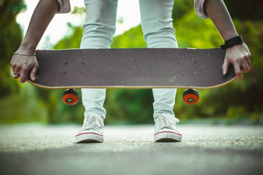 girl in white sneakers, holding a skateboard in hand close up