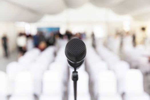 Microphone on the stage, blurred empty conference hall in the background