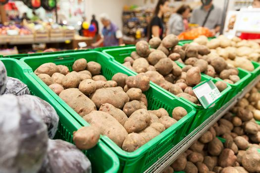 Potatoes on supermarket vegetable shelf, blurred buyers in the background