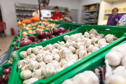 Garlic on supermarket vegetable shelf, blurred buyers in the background