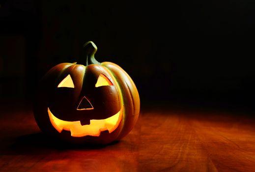Illuminated Halloween smiling spooky pumpkin on a dark background.