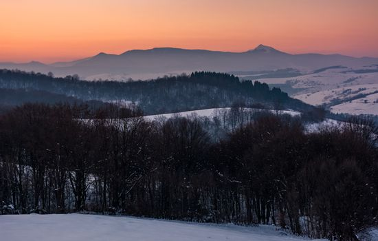 reddish winter dusk in mountains with high peak