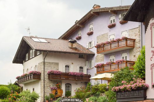 Mauve colored building with several balconies flourished in the dolomites in Italy