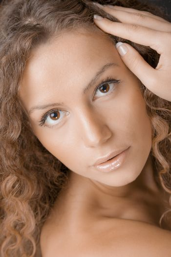 A portrait of a beautiful young woman with long curly hair.