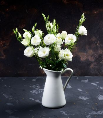 Elegant Flowers Bouquet with White Lisianthus and Decorative Green Stems in White Tin Jug closeup on Dark Grunge background