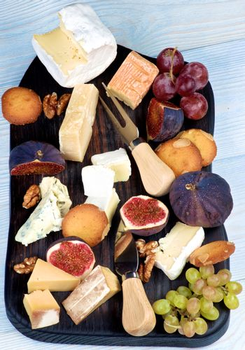 Gourmet Cheese Plate with Brie, Parmesan, Roquefort, Camembert and Herve Cheese, Figs and Grape with Biscuits on Slate Plate closeup on Wooden background. Top View