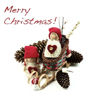 Christmas Decoration Concept with Handmade Dolls in Knit Hats, Fir Cones, Sleigh and Marshmallows on Wooden Sticks with Inscription closeup on White background
