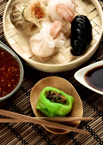 Assorted Dim Sum in Bamboo Steamed Bowl and Vegetarian Yasai on Wooden Plate with Red Chili and Soy Sauces and Chopsticks closeup on Straw Mat background