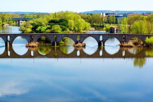 Bridge Puente de Piedra across River Douro with Water Reflection in Sunny Day on Cityscape background.  Zamora, Castilla and Leon, Spain