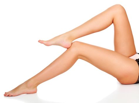 Closeup shot of beautiful long female legs isolated on white background