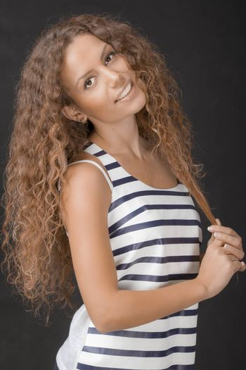 A young beautiful female with gorgeous hair standing and smiling. Studio shot.