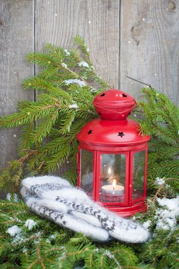 Red Christmas lantern with a candle and wool scandinavian style mittens