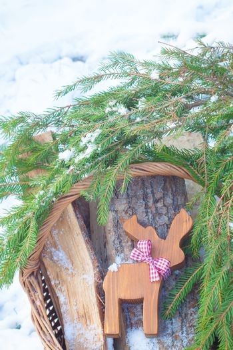 Christmas-tree toy on the basketful of firewood near snowy Christmas-tree