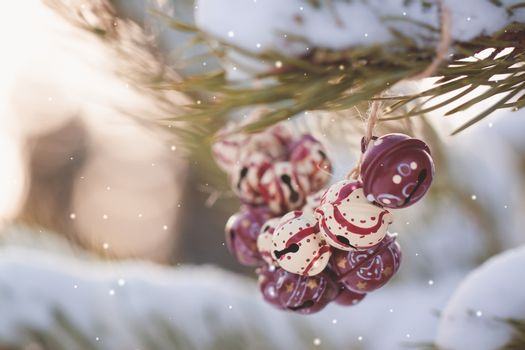 Christmas colorful vintage bells on the branches of a snowy tree