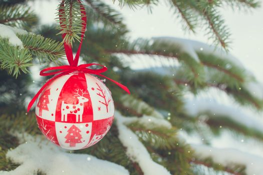 Scandinavian style red Christmas-tree toys on the snowy branches