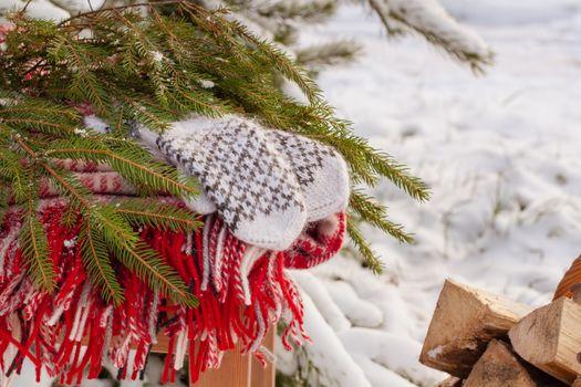 Scandinavian style wool mittens on the Christmas plaid near firewood